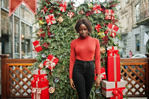 クリスマスの装飾、大晦日をテーマにポーズファッショナブルな赤いタートルネックを着て巻き毛のアフリカの女性の肖像画。