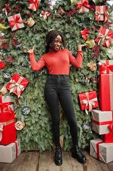 クリスマスの装飾、大晦日をテーマにポーズをとってファッショナブルな赤いタートルネックを身に着けている巻き毛のアフリカの女性の肖像画。