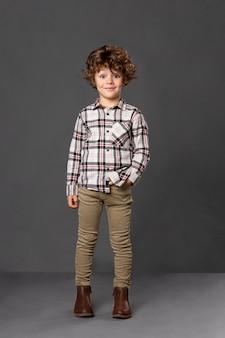 Портрет кудрявого маленького мальчика в повседневной одежде, концепция ребенка счастья, изолированная на сером