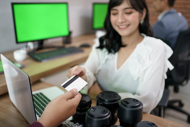 Портрет покупателя, оплачивающего счет кредитной картой в магазине проката фотоаппаратов