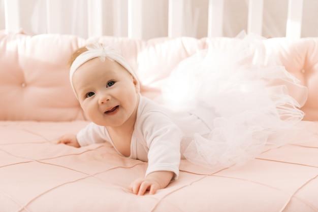 生後 6 か月のかわいい赤ちゃん、ベビーベッドに横たわる生まれたばかりの女の子の肖像画