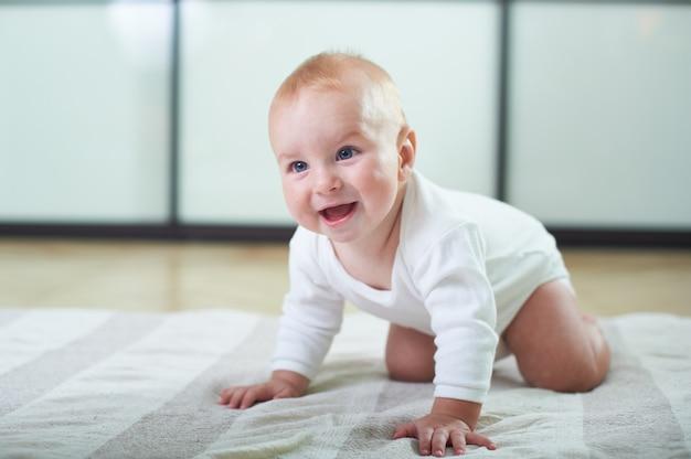 Портрет милый 6 месяцев мальчик ползет по полу