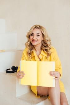 ヘッドフォンと黄色のノートブックと黄色の夏のスーツを着た、キュートで魅力的な笑顔の魅力的な女性の肖像画。ソフトセレクティブフォーカス。