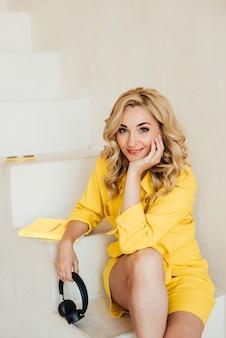 ヘッドフォンで黄色の夏のスーツを着てカメラを見ているかわいい、魅力的な、笑顔、魅力的な女性の肖像画。ソフトセレクティブフォーカス。