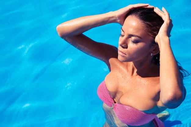 Портрет милой привлекательной женщины, стоящей в бассейне