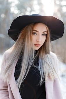 세련된 핑크 코트에 우아한 검은 모자에 금발 머리와 섹시한 입술과 갈색 눈을 가진 귀여운 매력적인 젊은 여자의 초상화