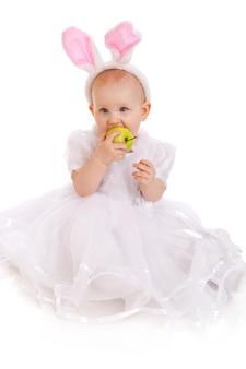흰색 배경에 녹색 사과가 분리된 부활절 토끼 귀를 입은 귀여운 아기의 초상화