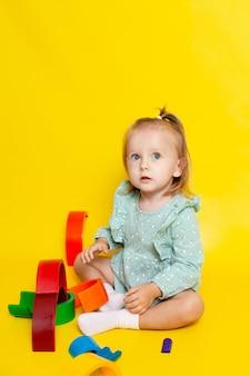 虹のデザイナーと遊んで、黄色の背景に青い目をしたかわいい女の赤ちゃんの肖像画。教育ゲームやおもちゃ。子供に教える。色。テキストの場所。高品質の写真
