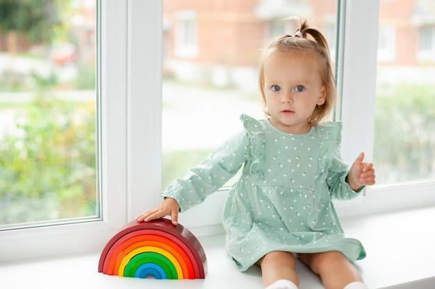 自宅でレインボーデザイナーと遊んでいる青い目をしたかわいい女の赤ちゃんの肖像画。教育ゲームやおもちゃ。子供に教える。色。テキストの場所。高品質の写真