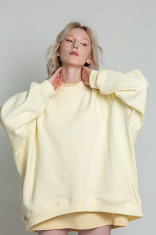 彼女の首に手をつないで特大の黄色のスウェットシャツでかわいい金髪の女性の肖像画