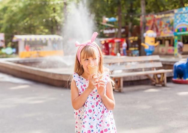 Портрет милой белокурой маленькой девочки с мороженым на прогулке в парке.