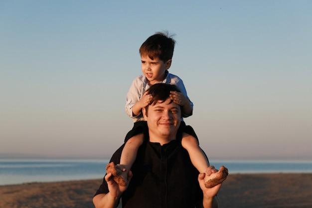 Портрет милого мальчика 3 лет на шее отца, идущего по пляжу в свете заката.