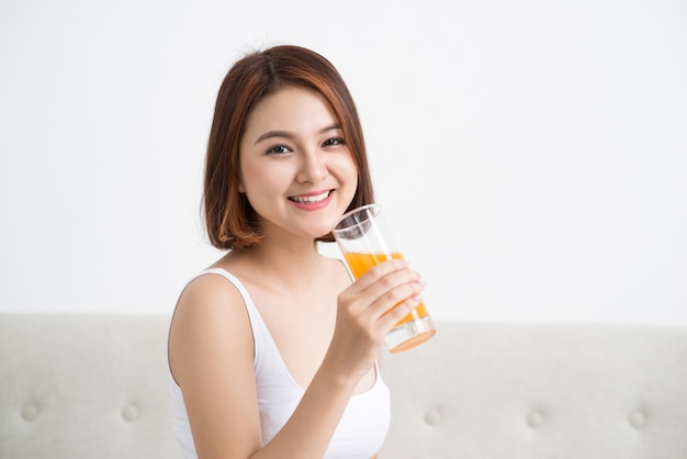 ガラスからオレンジジュースを飲むかわいいカジュアルな女の子の肖像画