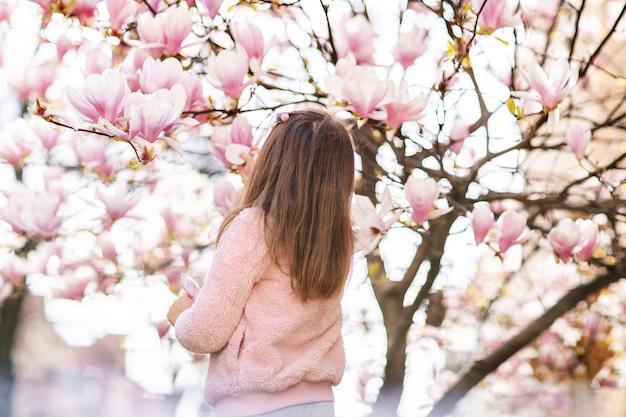 Портрет милой жизнерадостной девушки в сером платье в розовой куртке, отдыхающей весной в парке под цветущим розовым деревом магнолии.