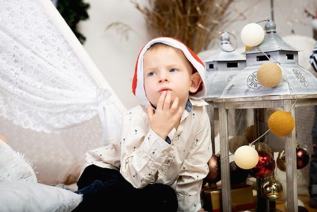 휴일 장식 사이에 앉아 크리스마스 모자를 쓰고 귀여운 아이 소년 아이의 초상화
