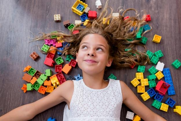 Портрет милой смешной девушки preteen играя с блоками игрушки конструкции. лежа на деревянном полу в окружении разноцветных блоков дети играют.