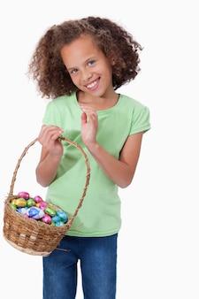 부활절 달걀의 전체 바구니를 들고 귀여운 여자의 초상화