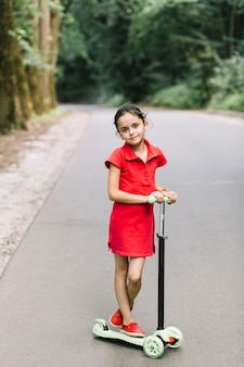 Portrait of a cute girl standing over scooters on road