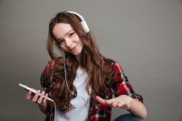 Портрет музыки милого подростка девушки слушая с наушниками