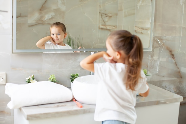창문이 있는 밝은 욕실에서 유니콘이 있는 흰색 코트를 입고 거울을 바라보는 귀여운 소녀의 초상화. 위생. 아침 루틴입니다. 청정. 엄마처럼. 고품질 사진