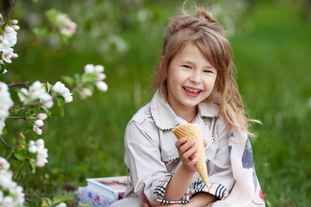Портрет милой девушки с мороженым на прогулке в парке. ребенок на открытом воздухе в цветущем весеннем саду