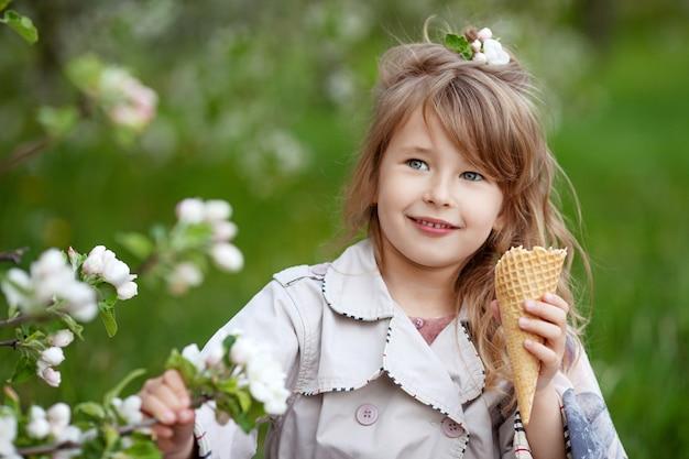 公園の散歩にアイスクリームとかわいい女の子の肖像画。花の咲く春の庭で屋外の子供
