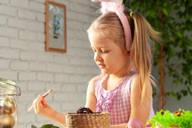 絵筆で卵をペイントする準備ができているかわいい女の子の肖像画