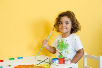 Portrait of a cute girl with paintbrush