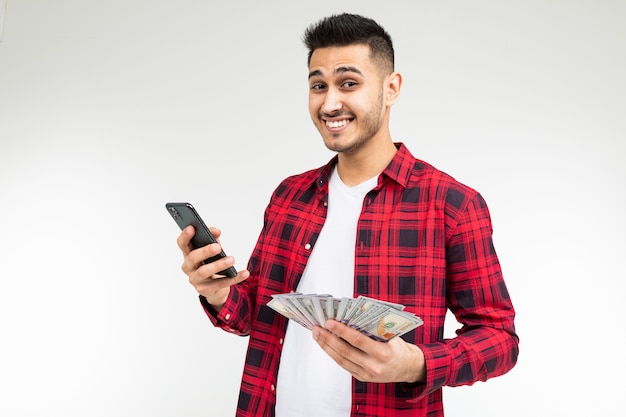 Портрет милый парень с кучей денег, разговаривает по телефону на белом фоне студии с копией пространства