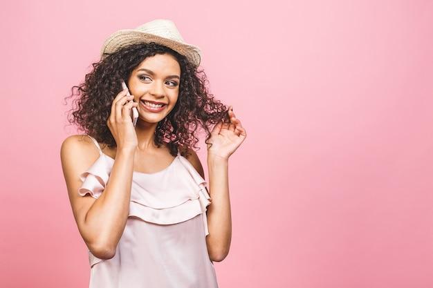 휴대 전화에 대 한 얘기와 분홍색 배경 위에 절연 웃 고 드레스에 귀여운 행복 아프리카 미국 여자의 초상화.