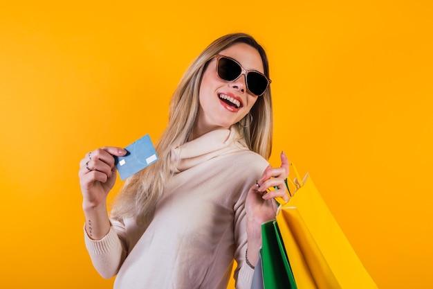 Портрет милой счастливой девушки с хозяйственными сумками и держа кредитную карту.