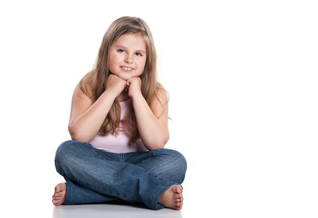 Портрет милой счастливой маленькой девочки, сидящей на полу, изолированной над белой