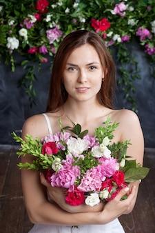 어두운 벽에 꽃을 들고 귀여운 행복 한 여자의 초상화. 스킨 케어 개념. 자연스러운 메이크업으로 아름 다운 여자