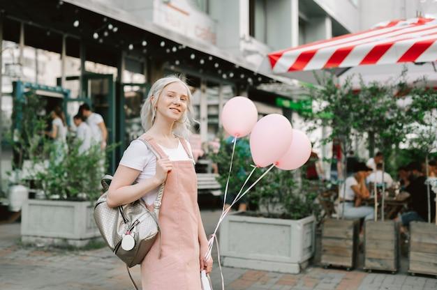 風船を持って通りを歩いているかわいい女性の肖像画