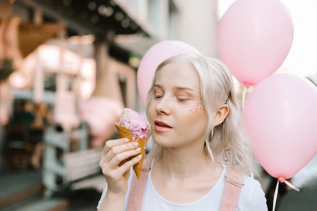 Портрет милой дамы, идущей по улице с мороженым и воздушными шарами