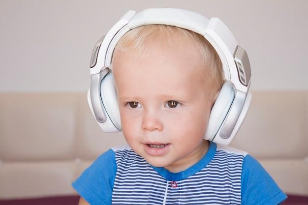 음악을 듣고 귀여운 작은 금발 소년의 초상화