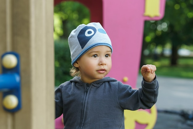 Портрет милого маленького мальчика. ребенок играет на детской площадке в городском парке.