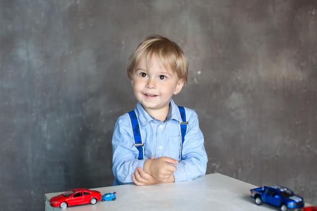 車、独立した子供のゲームで遊ぶかわいい男の子の肖像画。幼稚園のおもちゃの車で遊ぶ幼児男の子。就学前および幼稚園児向けの教育玩具。