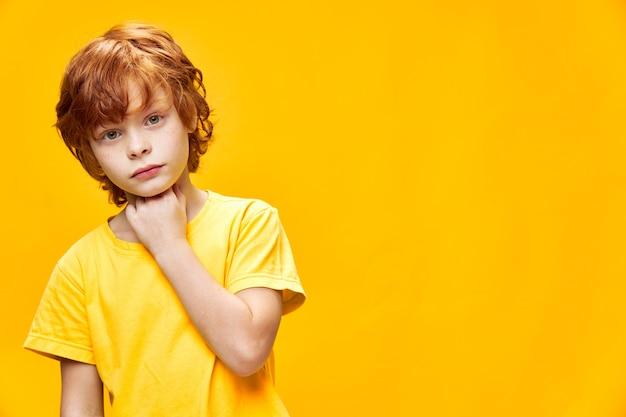 黄色いtシャツに生姜髪の正面図を持つかわいい男の子の肖像画興味のある表情の自由空間