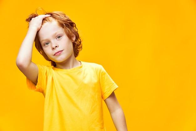 Портрет милого маленького мальчика с рыжими волосами, вид спереди, желтый изолированный фон, держит руки возле своего лица крупным планом