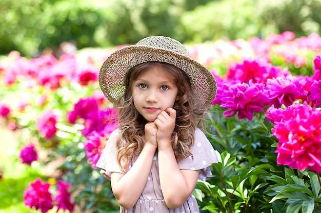 ベージュのドレス、明るい花と花壇の近くの都市公園で夏の日の麦わら帽子のかわいい小さなヨーロッパの女の子の肖像画。子供の頃の明るい瞬間。