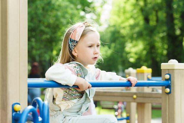 Портрет милой маленькой девочки. ребенок играет на детской площадке в городском парке.