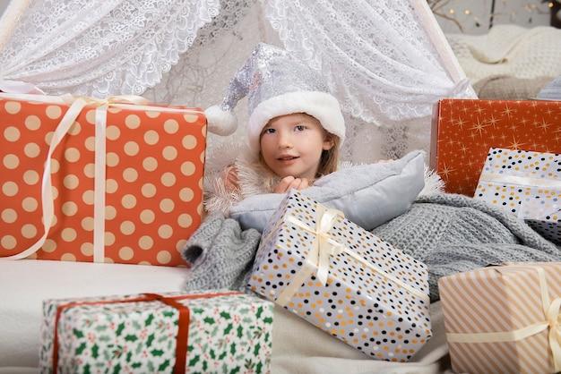 장식 된 house.merry 크리스마스와 해피 홀리데이 선물 상자 사이에 앉아 실버 색상 크리스마스 모자를 쓰고 귀여운 소녀 아이의 초상화!
