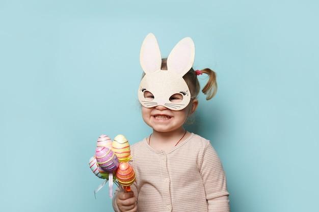 青い表面にカラフルな卵を保持しているイースターバニーの耳に身を包んだかわいい女の子の肖像画