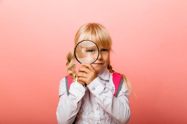 Портрет милой маленькой девочки, держащей увеличительное стекло возле ее глаза на розовом фоне.