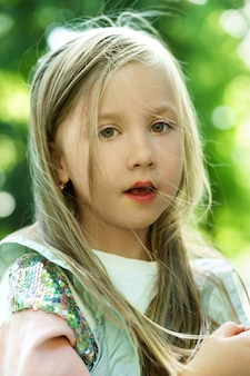 Портрет милой маленькой девочки в городском парке