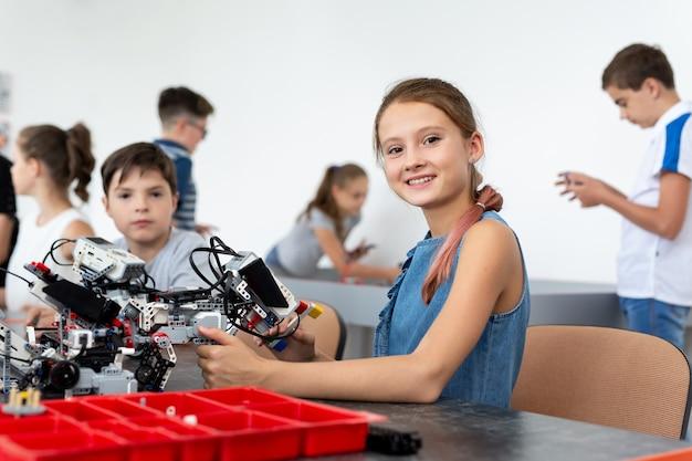 Портрет милой маленькой девочки в классе робототехники в школе
