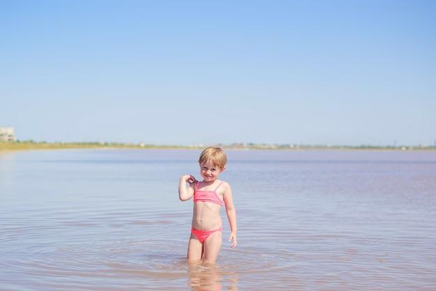 해변에서 분홍색 수영복에 귀여운 어린 소녀의 초상화