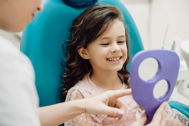 Портрет милой маленькой девочки, смотрящей на зубы после операции на зубах в детской стоматологии, сидя в кресле стоматологии.