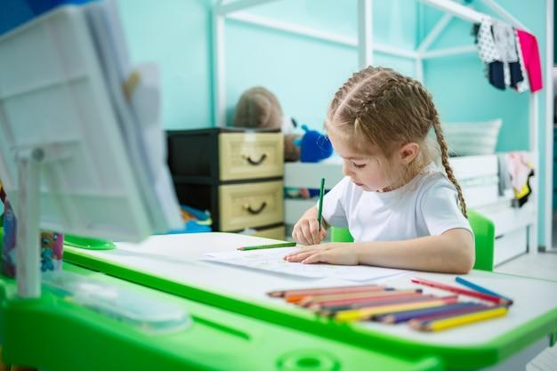 Портрет милой маленькой девочки, смотрящей в камеру и улыбающейся, рисуя картинки или делая домашнее задание, сидя за столом в домашнем интерьере, копируя пространство